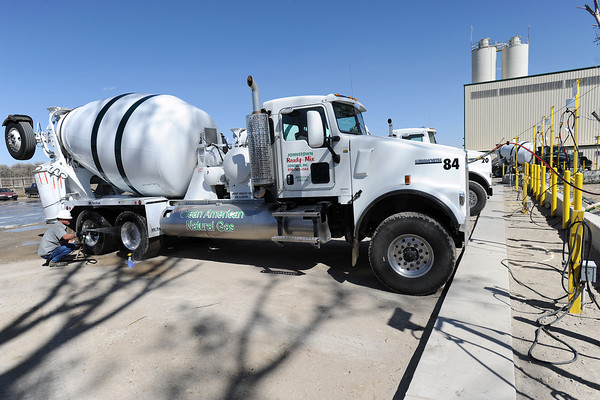 Scott Brumbaugh, a driver with Johnstown Ready-Mix, cleans the wheels on a concrete mixer truck as its tanks are filled with compressed natural gas at the fueling station on Thursday, March 29, 2012.