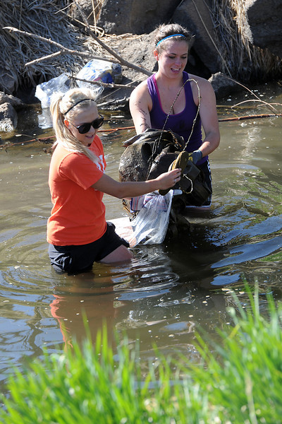 Thompson Valley High School seniors Emily Erickson, 18, left, and Shannon Galligan, 18, haul garbage from the Chubbuck Ditch near the Chilson Recreation Center while volunteering during the city of Loveland's annual spring waterway cleanup event.