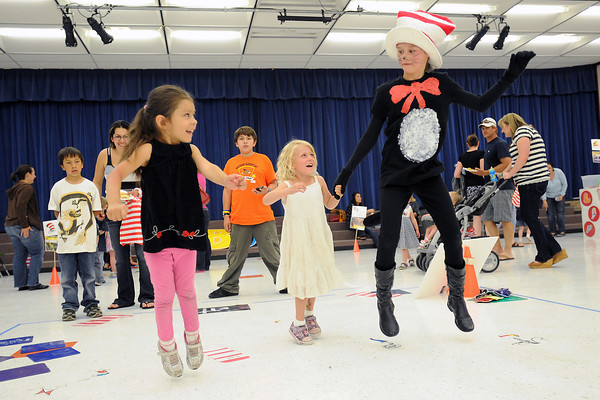 Nevaeh Jabalera, 4, left, and Bianca Garner, 5, play a leaping game with Morgan Madrid, 10, who's dressed as the Dr. Seuss character the Cat in the Hat during the Born to be a Reader Family Literacy Carnival on Thursday at Conrad Ball Middle School.