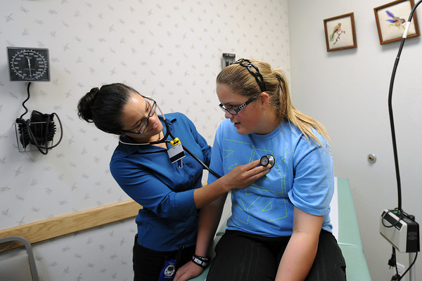 Dr. Marie Walsh, left, listens to twelve-year-old Destiny Chely's heart during her visit to the Loveland Community Health Center in downtown Loveland on Wednesday.