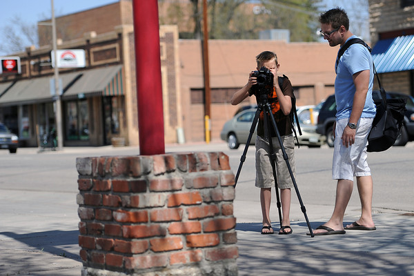 Ten-year-old Carsten Casteel takes a picture of the cube-shaped base of a sign while his father Jim Casteel looks on Friday afternoon in downtown Loveland. Carsten was working on an extra-credit assignment for school to show examples of angles, lines, flat shapes and solid shapes for his math class.