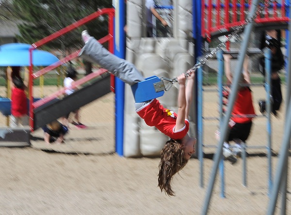 B.F. Kitchen Elementary School kindergartener Kyndle Payton, 5, swings on the playground Thursday at the school in Loveland. The school received a $250,000 grant to improve the outdoor play area.