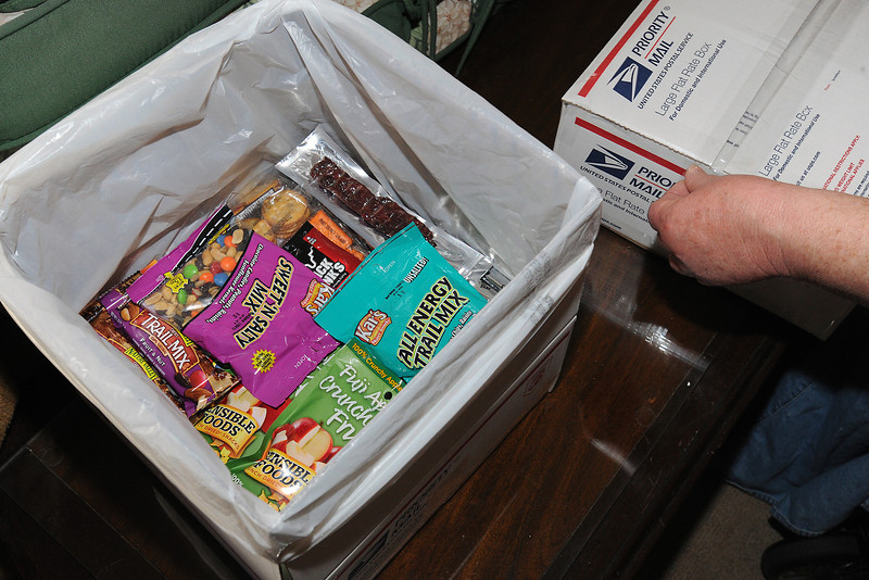 Jeanette Koniecki seals a box with tape as she prepares care packages Thursday, April 5, 2012 at her Loveland home to send to U.S. military members serving overseas as part of the Soldiers' Angels program.
