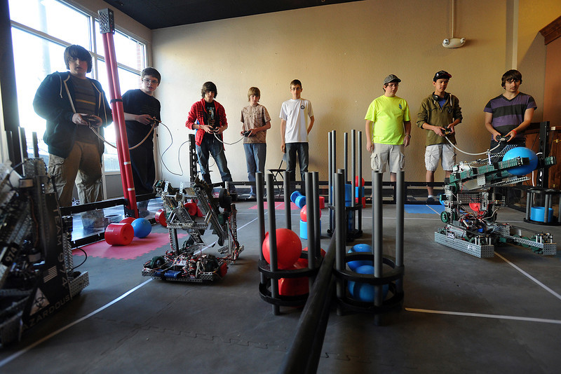 Robotics team players, from left, Mark Stewart, 14, Chase Rayment, 14, Arman Long, 14, Rhett Sandal, 14, Trey Gallagher, 13, John A.C. Miller, 17, Daichi Jameson, 14, and Michel Gross, 17, compete in a scrimmage on a practice field set up in downtown Loveland at 210 E. Fourth St. on Saturday, April 7, 2012.