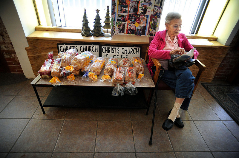 Glenda Stallings of Berthoud reads a book near a pile of bread intended for clients of the Front Porch, a nonprofit kitchen located inside the Christ Church of the Rockies at 310 N. Cleveland in Loveland. Volunteers, including Stallings' daughter, Terri Eggleston, from Grace Place in Berthoud staffed the kitchen Friday.