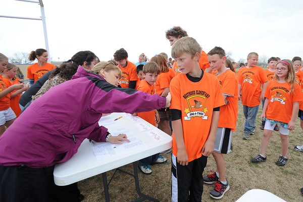 Jog-a-thon committee volunteer Alison Sandstedt, left, checks the back of fourth-grader Cooper Stratmeyer's T-shirt at the conclusion of the event to see how many laps he ran around the school's football field during the fundraising April 11, 2012. A mark was made on the back of each runner's shirt as they completed a lap.