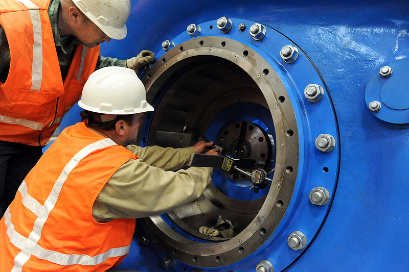 Dusty Williams, left, and Dave Martin, both with the Northern Colorado Water Conservancy District, cehck to make sure the generator shaft is centered inside the turbin case Wednesday as crews work to install equipment at the first hydroelectric plant at Carter Lake west of Loveland.