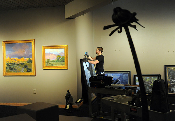 Quinn Johnson, exhibit preparator at the Loveland Museum/Gallery, hangs artwork Wednesday for the upcoming Colorado Governor's Invitational Art Show & Sale.
