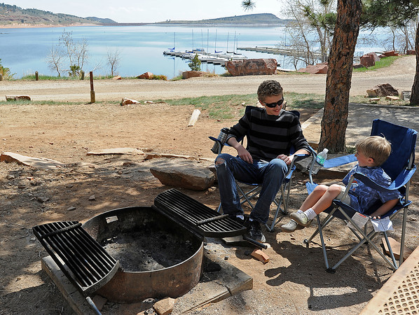 Reiss DeSandre, 14, left, and his little brother Chase DeSandre, 4, relax by a firepit while taking a break from fishing with their family Tuesday at Carter Lake west of Loveland. A fire ban is in place thursday in Larimer County and the Arapahoe and Roosevelt National forrest due to dry, warm conditions. Fires can still be burned in designated fire pits like this one at Carter Lake. Terri DeSandre, the boys mom, said she understands having a fire ban because of how dry it is but she is thankful they can still burn a fire in fire pits.