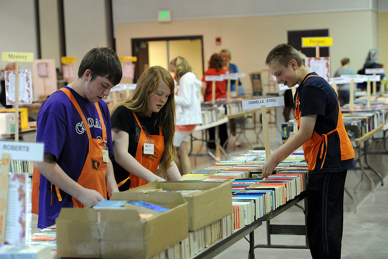 Friends of the Loveland Library volunteers, from left to right, Nick Baker, 15, Sarah Baker, 12, and Marcus Hill, 14, stock books during the Spring Book Sale in the 4-H Building at the Ranch on Saturday, April 28, 2012. The sale continues today from 11 a.m. to 3 p.m.