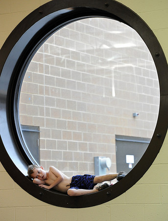 Taking a break from swimming, Tavin Adamson of Loveland, 7, relaxes in the window Monday at the Chilson Recreation Center. Tavin and other kids spent part of the day at Chuck E. Cheese and then went swimming as part of the recreation center's spring break day camps. Photo by Jenny Sparks