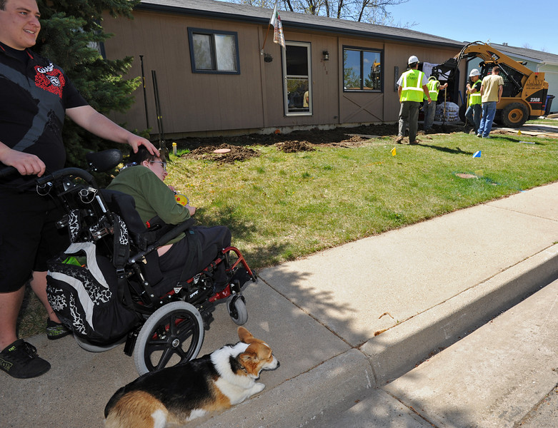Chris Dodge, left, pats his little brother Nick Dodge, 17, on the head as the two and their dog Hayley watch a crew from Coloraod State University work in front of their Loveland home Friday. The crew is building a wheelchair ramp and a front patio.