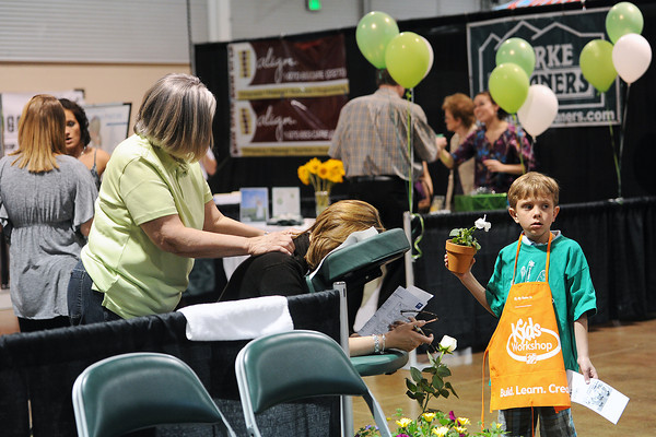 Six-year-old Jack Laugel, right, holds a plant he got from The Home Depot booth while his mother Mindy Laugel, middle, gets a free massage from massage therapist Jan Brown of The Spa at Scruples during the Loveland Chamber of Commerce's Business Expo on Wednesday, April 18, 2012 at The Ranch.