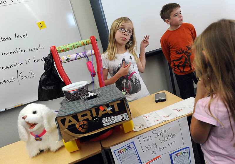 Coyote Ridge Elementary School fourth-grader Sora Lenz, 10, center, describes how her invention, the super dog walker, works to first-grader Hailey Nord, 7, right, Friday during the invention convention at the school. David Strasbaugh, 10, center right, waits to show off his invention, the candy catcher.
