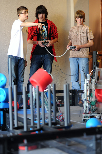 Robotics players from Altona Middle School's Arkham Asylum Members team, from left, Trey Gallagher, 13, Arman Long, 14, and Rhett Sandal, 14, compete in a scrimmage on a practice field set up in downtown Loveland at 210 E. 4th St.