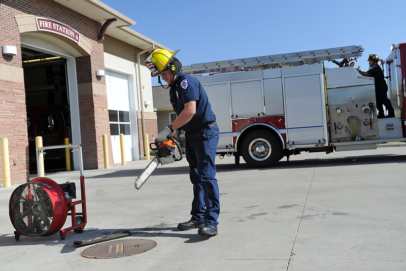 Loveland Fire and Rescue Lt. Dave Friedrichsen, left, and engineer Ron Hill, back right, perform a weekly small engine check Wednesday afternoon at Fire Station No. 6, 4325 McWhinney Blvd.