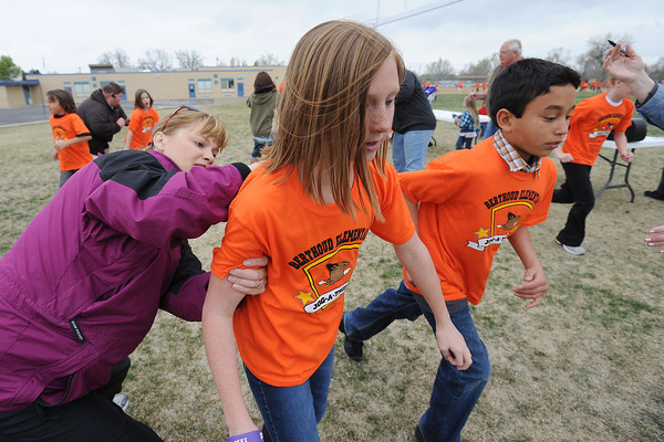Jog-a-thon committee volunteer Alison Sandstedt, left, marks on the back of fourth-grader Emily Cavey's shirt as she and classmate Derek Hofmeister complete a lap during the fundrasing event Wednesday, April 11, 2012 around the school's football field.