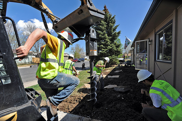 A crew from the Colorado State University Department of Construction Management's CM Cares community service initiative prepares an area before building a wheelchair ramp and a front patio Friday at the Loveland home of a teen named Nick Dodge, 17. From left to right they are Daniel Jones, Luis Covarrubias, Austin Shreve and Ian Darnell. Nick Dodge, center, watches the crew work from his wheelchair on the sidewalk.