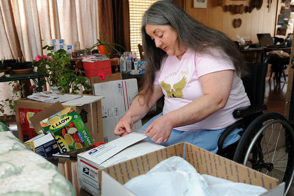 Jeanette Koniecki seals a care package at her Loveland home on Thursday, April 5, 2012 as part of the Soldiers' Angels program to send letters and packages to soldiers serving overseas in the military. Koniecki sends a variety of items including food, sun screen, toiletries, socks, books and movies in the packages.