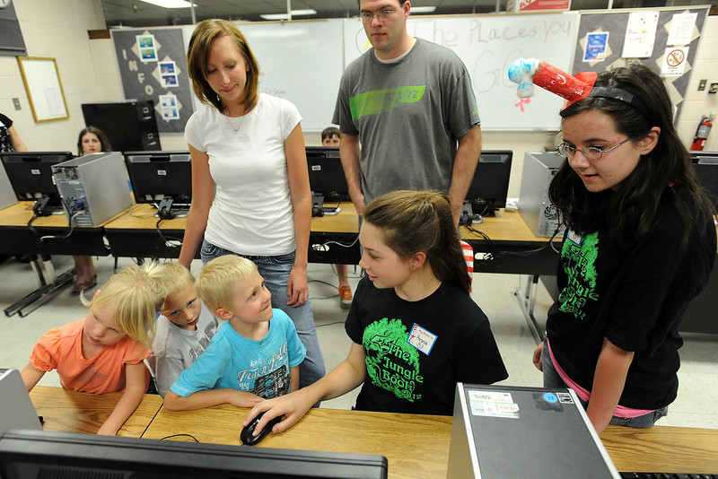 Conrad Ball Middle School sixth-graders Dusty Bergland, 12, right, and Anna Mueller, 12, assist Tyler Jamison, 5, Jackson Jamison, 6, and Jayna Jamison, 2, as they make a little book on a computer at the school during the Born to be a Reader Family Literacy Carnival on Thursday, April 26, 2012. Looking on are Traci and Jason Jamison.