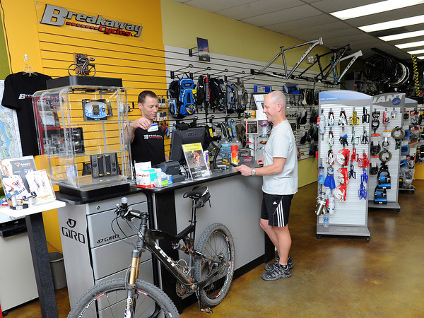 Breakaway Cycles owner Rich Panozzo, left, rings up a sale to Loveland resident Andy Artzberger on Tuesday afternoon at the bike shop located at 2237 W. Eisenhower Blvd. Larimer County officials will reduce a sales tax to pay for the county courthouse earlier than planned.
