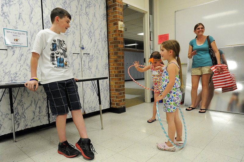Conrad Ball Middle School sixth-grader Alex Gray, 12, left, helps Riley Vance, 5, front right, and her twin sister, Carly as they try out hula hoops at one of the stations set up for the Born to be a Reader Family Literacy Carnival on Thursday, April 26, 2012.