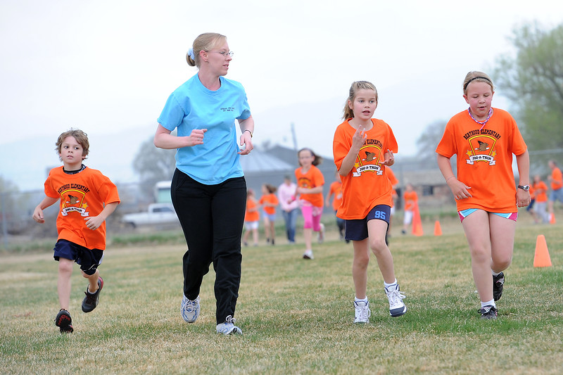 Caleb Francis, left, Shan Holt, Olivia Dunn and Amber Holt run around the football field at Berthoud Elementary School during the Jog-a-thon April 11, 2012.