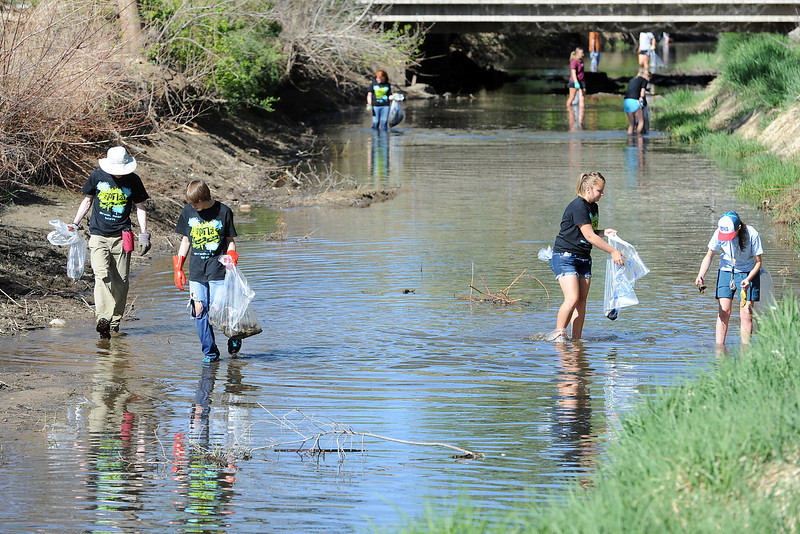 Volunteers spread out along a stretch of the Chubbuck Ditch near the Chilson Recreation Center during the annual spring waterway cleanup. Front from left are Kyle Kluherz, 18, Riley McLeran, 17, Sara Trout, 18, and Molly Shea, 18, who were among a group of students from Thompson Valley High School who turned out for the event.
