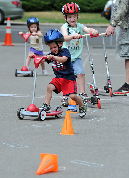 Barrett Thalman, 2, front, Will Thalman, 4, center, and Brooklyn Thalman, 2, go through the bike skills course on scooters Wednesday during Children's Day in Loveland.