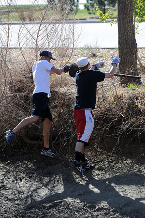 Gus Waneka, 18, left, and Chad Eberl, 17, toss a metal pole with a concrete base up on the bank of the Chubbuck Ditch after fishing it out of the water during the annual spring waterway cleanup Saturday, April 21, 2012.