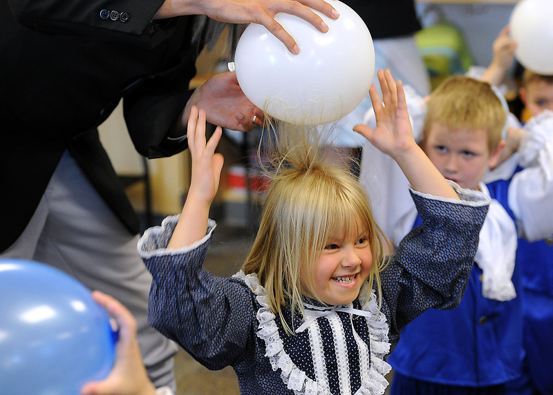 Loveland Classical Schools first-grader Allison Goss, 6, giggles as her science teacher Ian Stout lifts a balloon off her head and her hair stands up Friday during the school's first Colonial to American Revolution Day. Students were learning about static electricity by rubbing balloons on their heads.