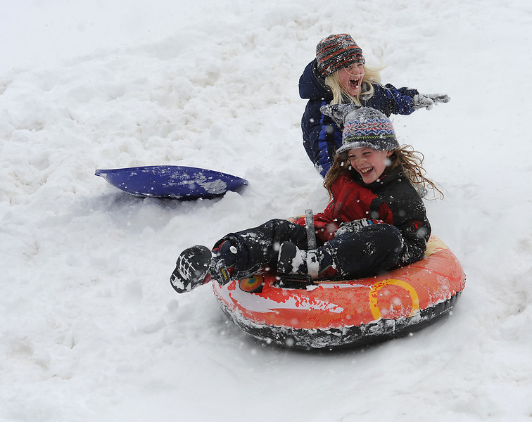 "Zion Downing, 5, back, tries to jump on as his big brother, Storm Downing, 7, sleds down a hill at North Lake Park in Loveland on Wedneday, April 17, 2013. After playing in the snow, Zion said ""This is the best day ever!"""