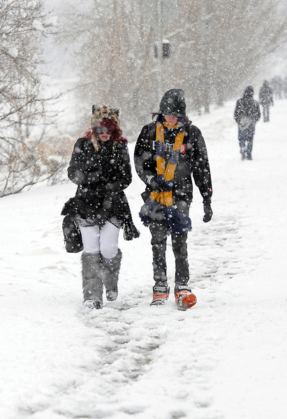 All bundled up as the snow falls, MeKenna Cogan, 15, left, and Cole Scott, 18, walk home from school on Taft Avenue near 29th Street in Loveland on Wednesday, April 17, 2013.