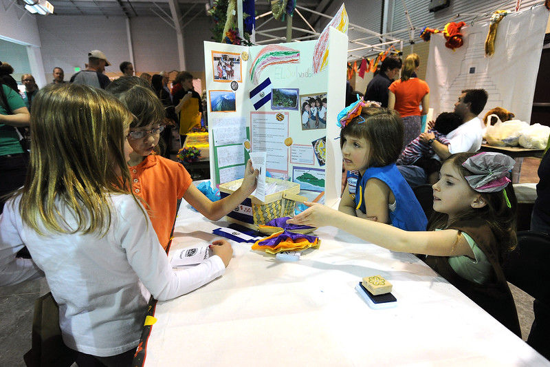 Annalise Killen, 7, left, and Bridget McGowen, 8, have their passports stamped by Girl Scouts Maddie Baran, 8, right, and Lily Evans, 6, at their El Salvador booth during the 48th Annual Northern Colorado International Festival on Saturday, April 13, 2013 at The Ranch.