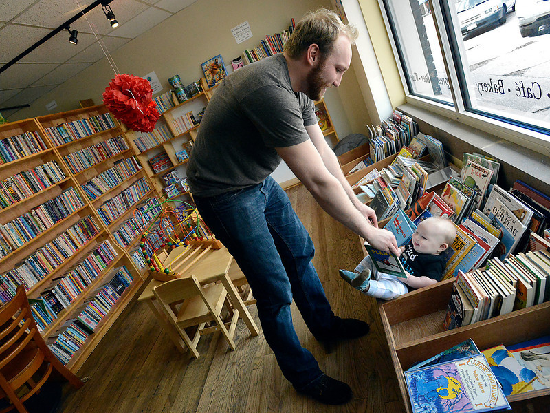 Andrew Webb plays with his baby, Adler Webb, 5 months, in the children's book section of Anthology Book Co. in downtown Loveland on Thursday, April 25, 2013. Webb and his wife, Jenn Webb, will be managing Anthology Book Co. Powered by 3 Coffee & Roastery, after the bookstore's owners formed a partnership with 3 Coffee of Milliken.