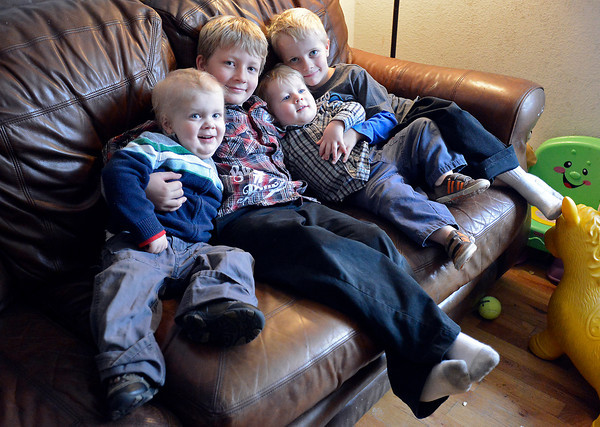 The Green brothers pose for a photo while snuggling on the couch in their Loveland home. From left they are Joel, 4, Caleb, 7, Elijah, 2, and Isaac, 5.