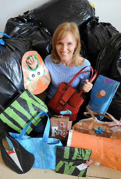 Heather Rubald poses for a photo surrounded by recycled trash bags holding purses and other itmes she makes out of the plastic bags in Loveland on Thursday, April 25, 2013.
