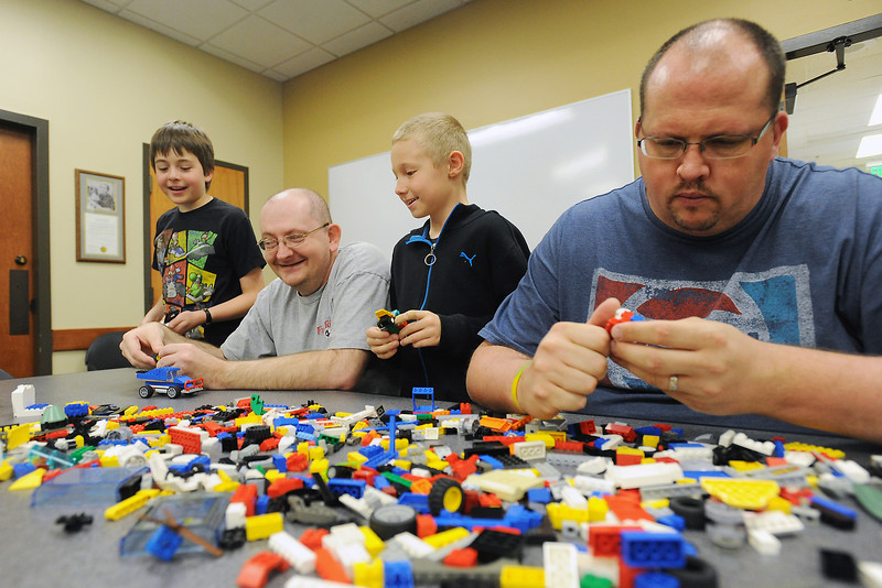 Curtis Mork, right, assembles LEGO pieces with, from left, Cameron Stornetta, 11, Michael Miller, and Jack Grindle, 9, during the Cogs and Clockwork event put on by Mork on Saturday, April 6, 2013 at the Loveland Public Library. Participants learned about the history of the toy and were allowed to build things using some of the many LEGO bricks in Mork's collection.