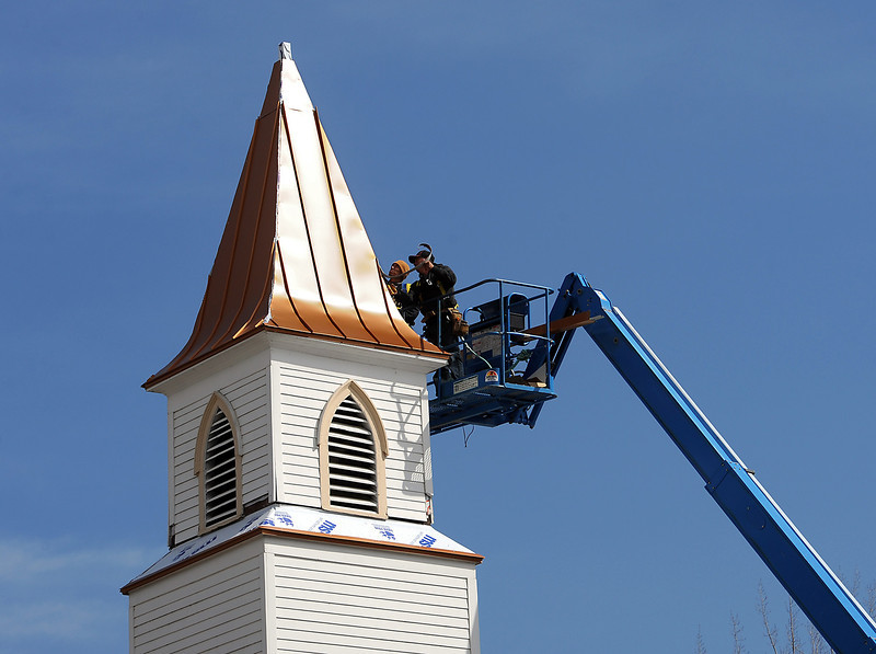 Roberto Castro, left, and Remiro Lopez, both with Westers Roofing, install copper roofing on the 50 foot steeple at the Loveland Bible Church on Monday, April 1, 2013.