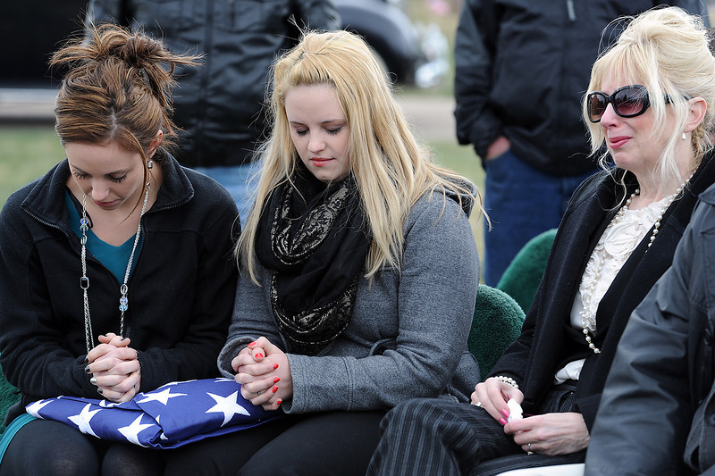 Brittany Foster, left, and Mariah Foster, center, bow their heads in prayer after being presented with a flag in honor of their grandfather, WWII veteran Donald Galbraith, as their mother, Erin Foster, right, tries to hold back tears during a burial ceremony for Galbraith at Resthaven Memorial Gardens in Loveland on Thursday, April 11, 2013. Galbraith, who died March 20, was honored with a 21-gun salute, trumpeters playing taps and bagpipe music during the burial. He joined the Navy on May 4, 1943 and fought during some of the most important battles in the Pacific, including Iwo Jima and Okinawa.