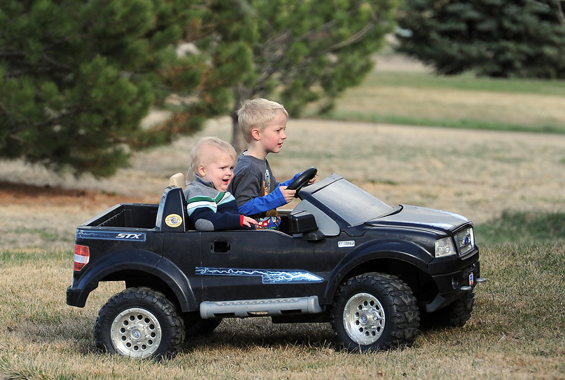 Isaac Green, 5, drives his little brother Joel, 4, around in their power wheels truck Thursday outside their Loveland home.