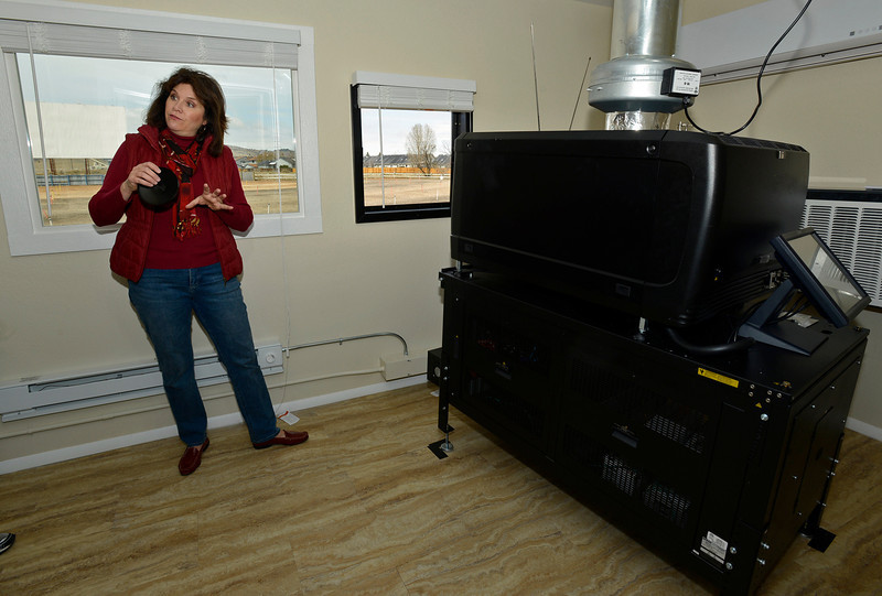 With the movie screen in the background, Stephanie Webb, co-owner of the Holiday Twin Drive-in theater, explains how their new digital projectors work in Fort Collins on Wednesday, April 10, 2013.