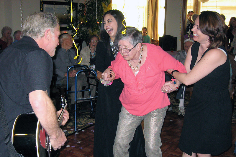Steve Manshal, from the band Firefall, left, serenades Mariana Luxenberg, who is in the middle dancing with The Hillcrest of Loveland staff members Jamie Felton and Jesseca Tighe, during the ÒSeniorÓ Prom on Friday.