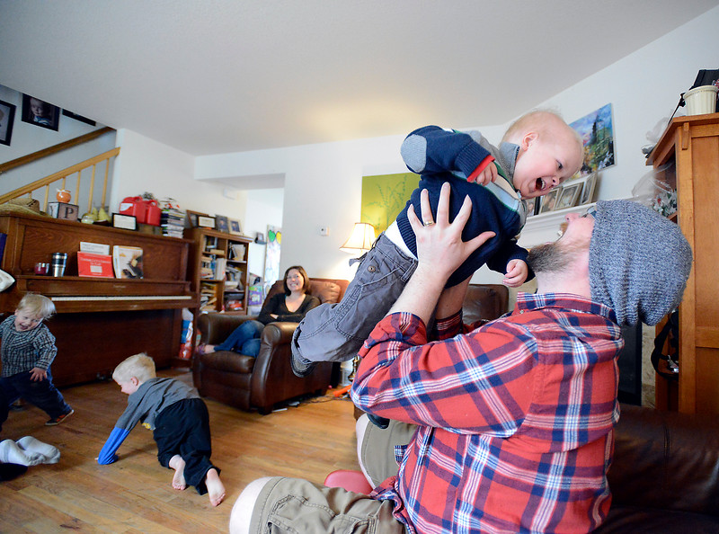Joel Green, 4, plays with his dad, Ryan Green, as his brothers romp around their Loveland home Thurdsay.
