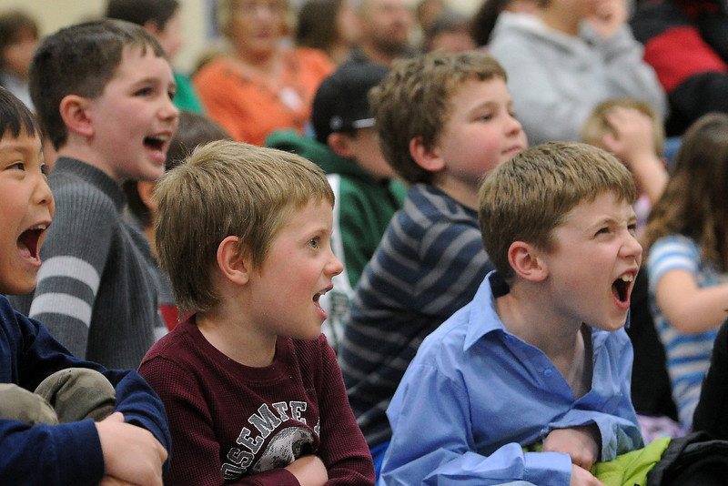 "Family Literacy Night attendees, front from left, Matthew Phillips, 8, Noah Kreutzer, 5, and Isaac Kreutzer, 7, yell out the phrase ""I can do that,"" while listening to a presentation by author Michael Anthony Steele on Tuesday, April 16, 2013 in the gymnasium at Namaqua Elementary School."