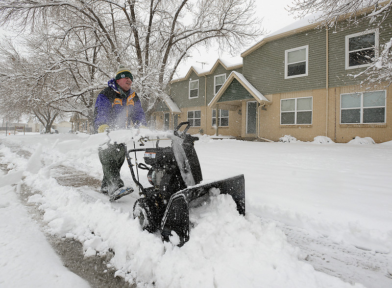 Zach Sauer uses a snow blower to clear snow in front of townhomes on the 1600 block of Carlisle Drive in south Loveland on Monday, April 15, 2013.