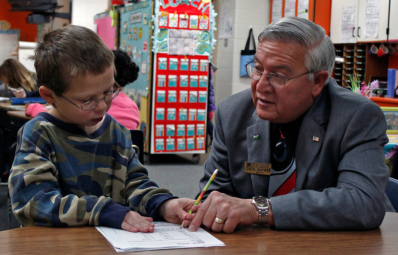 Loveland Mayor Cecil Gutierrez helps Lincoln Elementary student Seth Rodgers (8) with his in-class assignment Tuesday morning while visiting the school during the Mayor's Day of Recognition for National Service in Loveland, Colo.