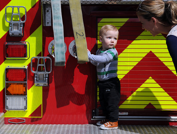 Asher Girard of Loveland, 15 months, looks back at his mom, Britni Girard as he tugs on a fire hose while standing on the back of a Loveland Fire Rescue Authority truck during Children's Day in Loveland on Wednesday, April 24, 2013.