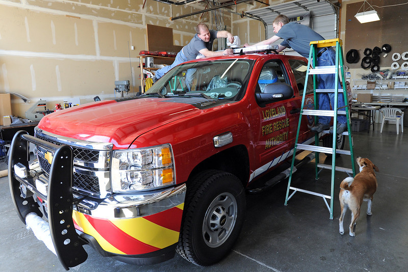 Recreational Electrical owner Patrick Jiles, left, and employee David Walsh mount a robotic spotlight on top of a new Loveland Fire Rescue battalion chief vehicle on Friday, April 19, 2013 while shop dog Kunu looks on as they work. Recreational Electrical, at 459 N. Denver Ave. in Loveland, specializes in installing electrical systems on emergency vehicles, hot rods, semis, recreational vehicles and boats. Jiles said the almost $20,000 job for Loveland Fire Rescue involved installing a custom package of lights and sirens, radios, a push bumper, a rear sliding tray and cabinetry for the electronics. The company also will be outfitting a brush truck for the department, he said.