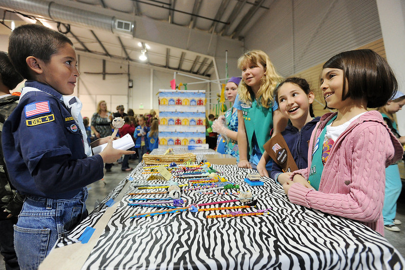 Dante Martinez, 8, left, looks at items for sale at the Zambia booth being run by Girl Scouts, front to back from right, Avril Martinez, 10, Dakota Moon, 8, and Maddy Hasstedt, 11, during the 48th Annual Northern Colorado International Festival on Saturday, April 13, 2013 at The Ranch.